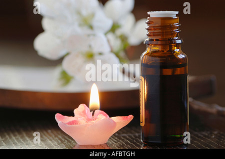 Bottle of scented oil, beside a candle, close-up