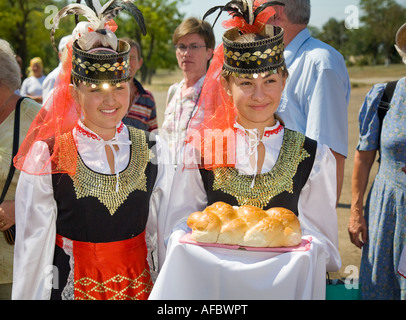 Young girls in traditional Ukrainian costume, conveying to a group of visitors the traditional welcoming present, - Stock Photo