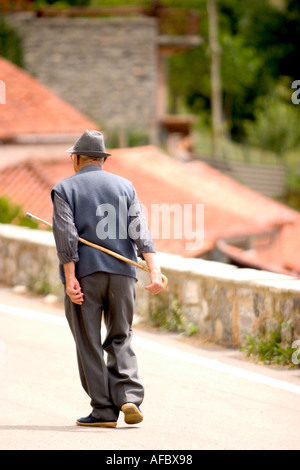 old man walking in the village and using a cane stick - Stock Photo