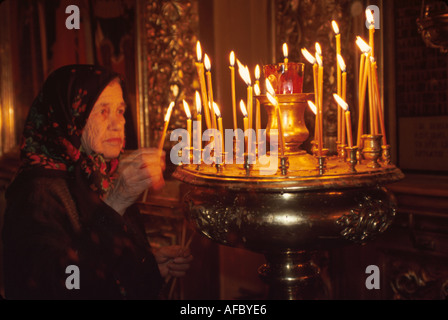 Russia former Soviet Union Moscow Orthodox church interior senior woman lights memorial candles - Stock Photo