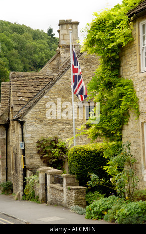 Union Jack flag flying on War Memorial in Castle Combe Wiltshire England UK - Stock Photo