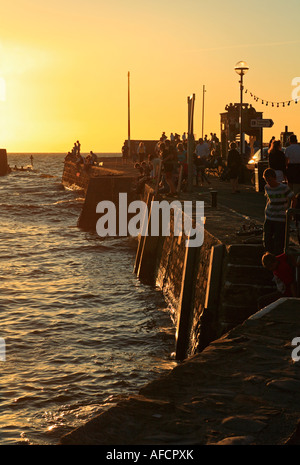 People catching crabs at Aberaron Harbour, Wales, at sunset. - Stock Photo