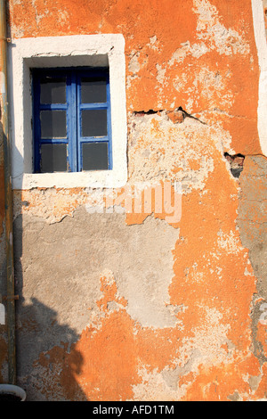 small window in painted wall of dwelling house, Greece - Stock Photo