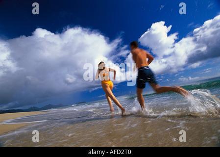 Couple jogging along the beach, Porto Santo, Madeira, Portugal - Stock Photo