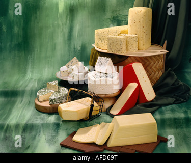 Danish Cheeses in group color photograph on green toned mottled background. Horizontal  Format, studio tabletop. - Stock Photo