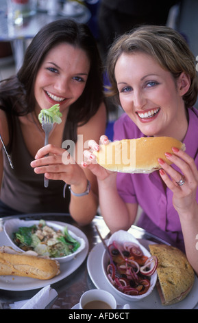 2 young women in a restaurant eating healthy foods - Stock Photo