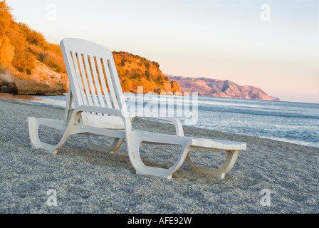 Isolated lawn chair sitting on lonely beach - Stock Photo