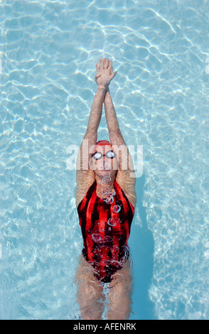 A women swimmer is seen from above as she pushes off the wall on her back in an outstretched, tight, streamline - Stock Photo
