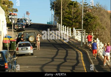 A woman in bikini standing near her SUV on a road near Bondi beach, Sydney, Australia - Stock Photo