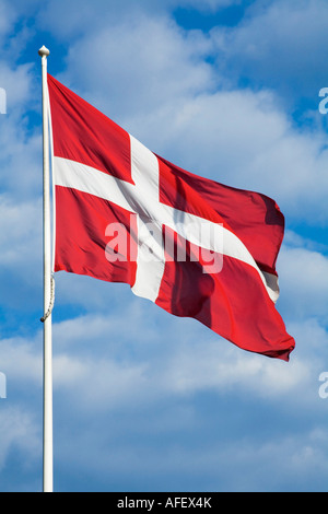 Danish Flag against a blue sky with clouds - Stock Photo