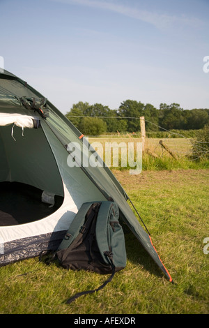 A rucksack and tent pitched in the New Forest, England - Stock Photo