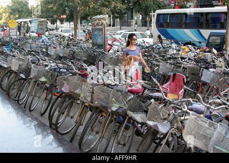 young chinese girl walking among bicycles Yinchuan town Ningxia China August 2007 - Stock Photo