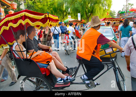 Beijing CHINA, Old Neighborhoods Street Scene Hutongs Tourist Couple Riding in Rickshaw in 'Houhai Lake District' - Stock Photo