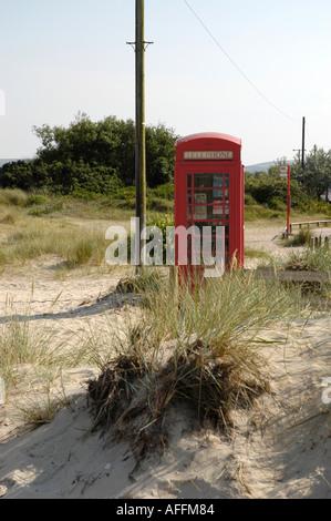 Red K6 telephone box on a beach at sandbanks in Dorset - Stock Photo