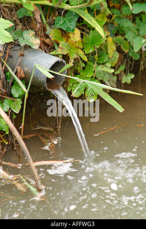 Water running through pipe into river - Stock Photo