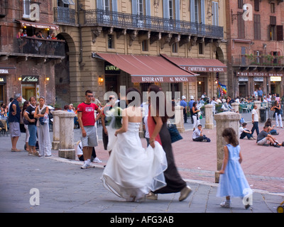 Bride in wedding dress with maid of honor and flower girl walking through the Piazza del Campo Siena Italy - Stock Photo