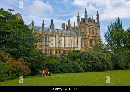 Couple sitting on a bench with the Houses of Parliament behind London England UK - Stock Photo