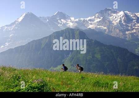 On a hiking tour near Grindelwald in front of Mt Eiger, Mönch and Jungfrau Bernese Oberland Switzerland - Stock Photo