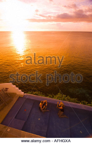 Couple relax in an infinity pool  at Vatulele Island Resort as the sun sets across the South Pacific Fiji - Stock Photo