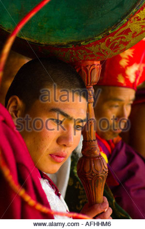 Monks drumming at watching masked dancers performing the Dance of the Terrifying Deities at the Paro Tsechu Festival - Stock Photo