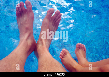 Young Girl s Feet Age 5 8 and Her Father s Dangling in Swimming Pool Stock Photo
