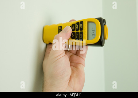 using an ultrasonic measure held against a wall for reference point - Stock Photo
