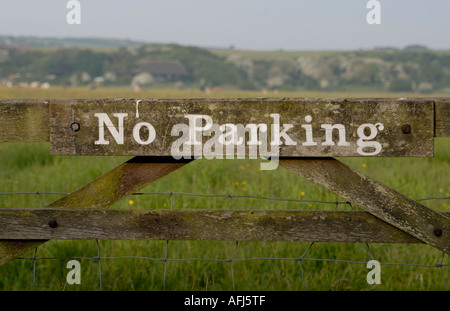 A No Parking sign on an old wooden five bar gate leading into a flower filled meadow Cuckmere Haven Sussex - Stock Photo