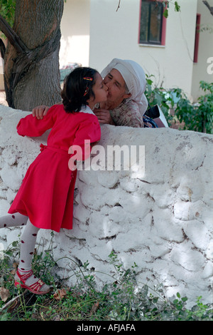 Young Turkish school girl greeting her grandmother in small village in South Western Turkey. - Stock Photo