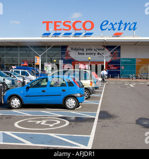 Provision made for disabled car drivers by provision of designated car parking bays at a large supermarket store - Stock Photo
