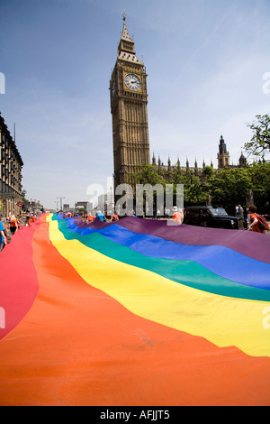 A giant rainbow flag is passing by the British Parliament during the gay parade of the EuroPride London - Stock Photo