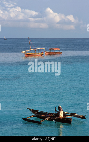 Fisherman sets out in his dug out outrigger canoe Nungwi Northern tip of Zanzibar Tanzania East Africa - Stock Photo