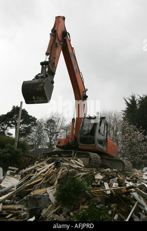 orange fiat hitachi JCB on construction site removing demolished old building west belfast northern ireland - Stock Photo