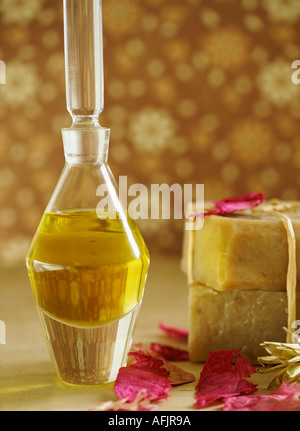 Bottle of oil, natural soaps and petals against a brown floral background - Stock Photo