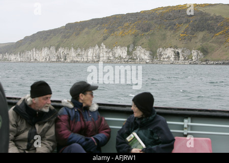 tourists on board the Caledonian MacBrayne MV Raasay  ferry look at limestone cliffs on Rathlin Island en route - Stock Photo