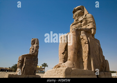 The Colossi of Memnon stand at the entrance to the ancient Theban Necropolis on the West Bank of the Nile at Luxor. - Stock Photo