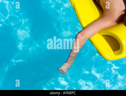 Girl on raft in swimming pool with arm in water - Stock Photo
