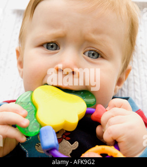 Baby boy chewing on rattle - Stock Photo