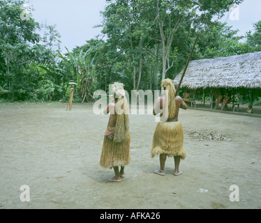 Peru Amazon two Yagua indian men at blowpipe practice 2004 in the arena of their homestead - Stock Photo