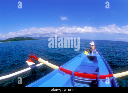 Woman sitting on bow of boat off the coast of Lombok Island in Indonesia Model Released Photo - Stock Photo