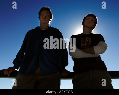 Silhouette of two teenage boys against sky - Stock Photo