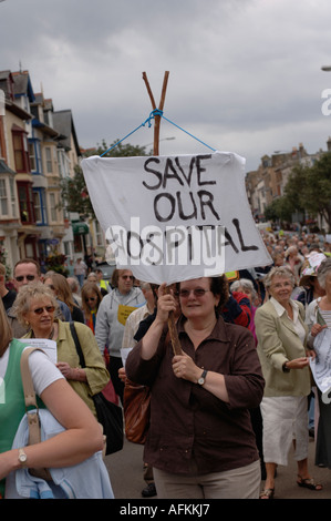 A crowd of people marching protesting against planned downgrading of Bronglais general hospital Aberystwyth Ceredigion - Stock Photo