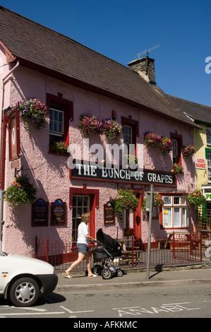 woman pushing pram passed the pink painted Bunch of Grapes inn pub Newcastle Emlyn Carmarthenshire wales cymru - Stock Photo