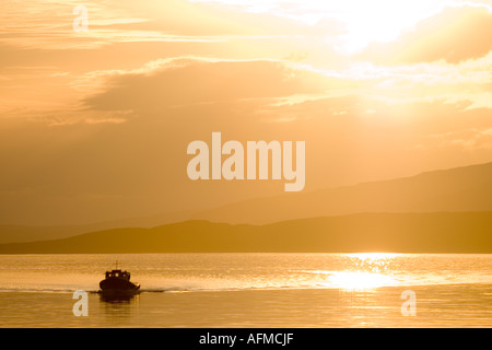 Sunset over Mull, with a passenger boat in the foreground. - Stock Photo