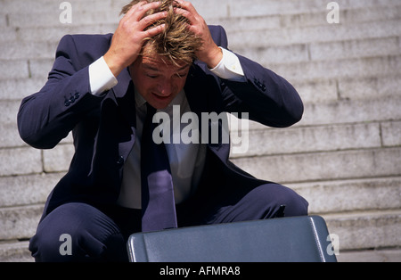Man with head in hands staring at open briefcase - Stock Photo