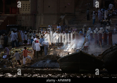 Pouring sacred Ganges water on the ashes at the cremation site on the banks of the Ganges Varanasi India - Stock Photo