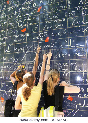 three adolescent teenagers pointing at text 'I love you' on Parisian Love wall Place des Abbesses Paris France - Stock Photo