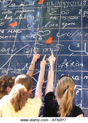 three adolescent teenage girls pointing at text 'I love you' on Parisian Love wall Place des Abbesses Paris France - Stock Photo