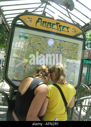 two teenage girls looking at map of paris underground system at entrance to place des abbesses