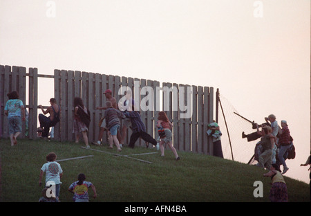 Rioting deadheads jump a fence to enter a Grateful Dead show at Deercreek Indiana during July 1995 - Stock Photo