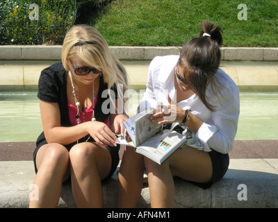 two young women looking at guide book of Paris planning their day Jardin du Forum des  Halles Paris France - Stock Photo